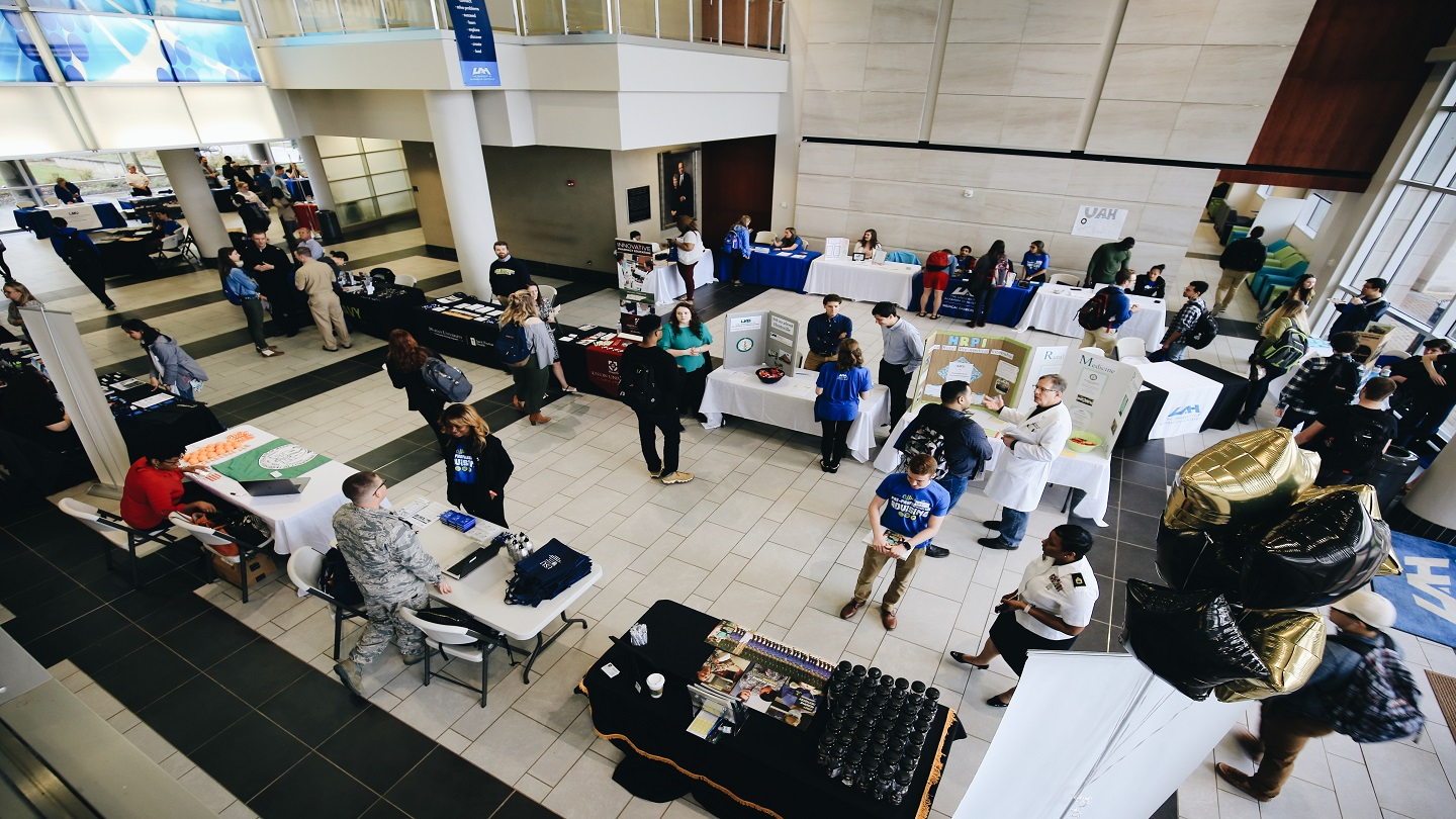 overhead view of the health careers day event. a crowded room with people standing around booths looking at presentations and talking to vendors