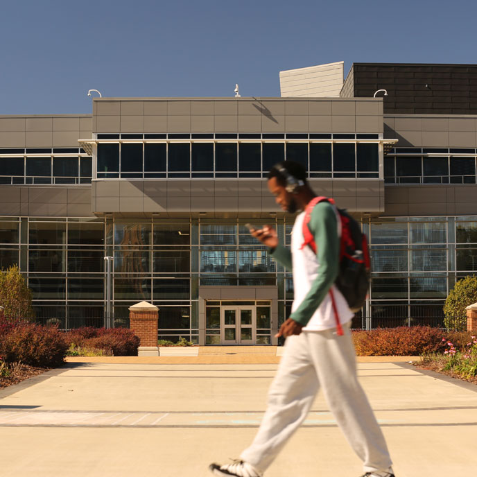 a male student walking across campus at UAH