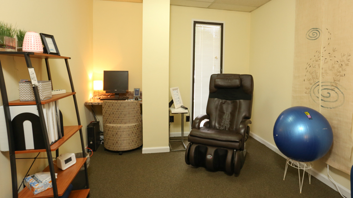 A room with a massage chair and meditation equipment