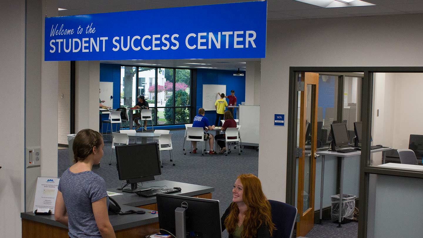 The Student Success Center front desk. A student is standing at the desk talking with a SSC member.