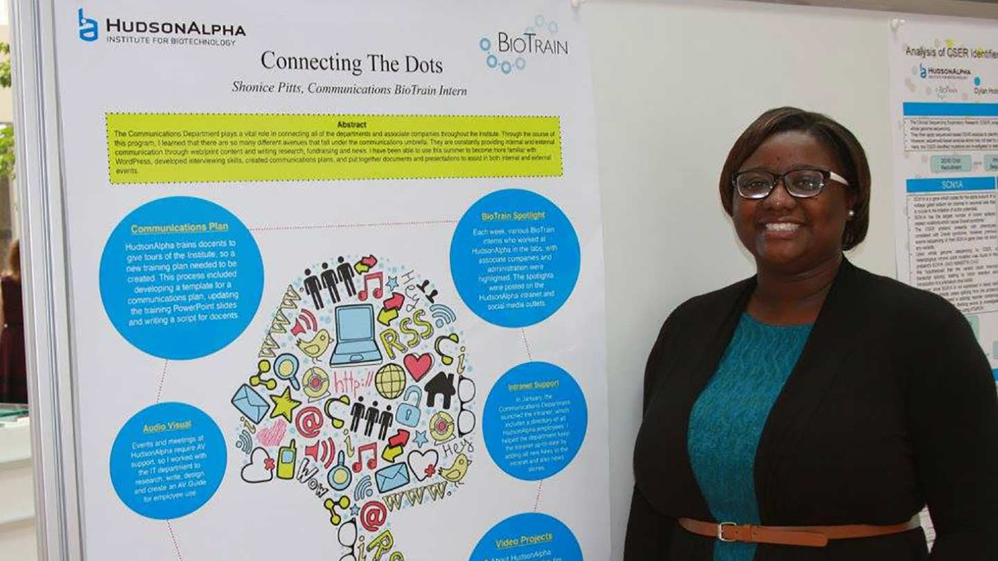 Intern Shonice Pitts standing next to a poster illustrating her internship.