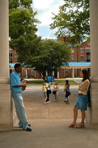 Students talking under column entrance-way.