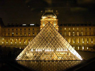 Glass pyramid in front of the Louvre at night.