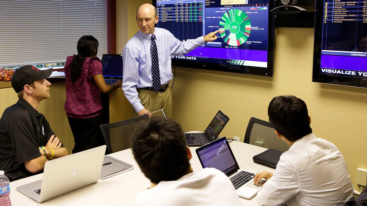 Students setting at a table as a professor points to data, graphics, and charts displayed on a TV monitor