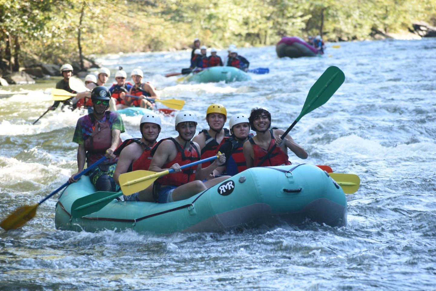 Honors College mentors rafting rapids on a river