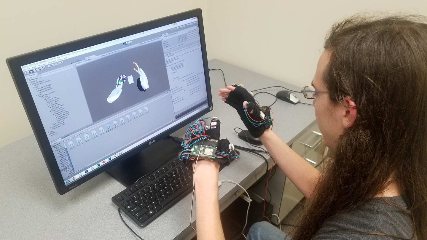 a young male college student at UAH conducts research with virtual reality gloves on a desktop computer