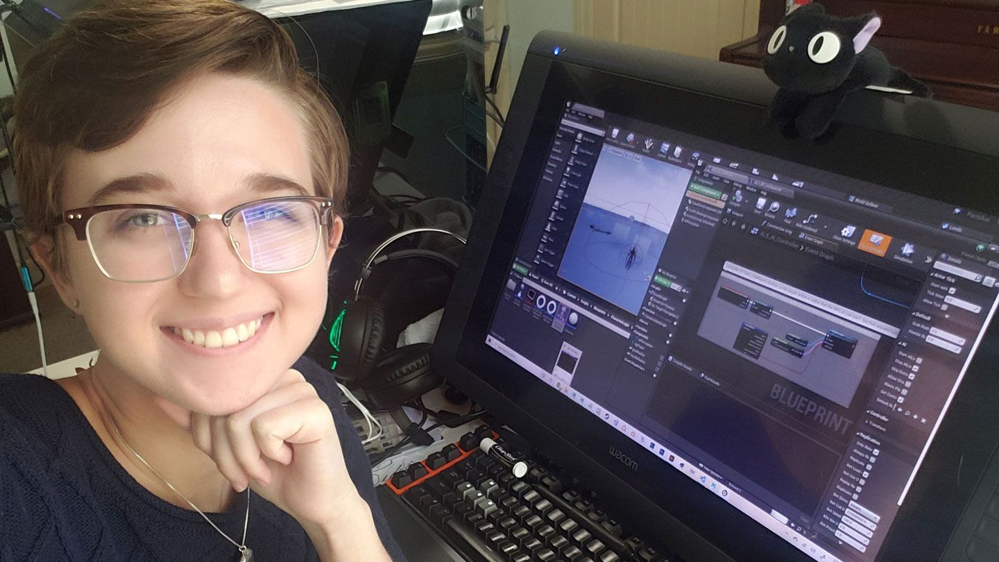 a young woman college student at UAH with short hair and glasses works on a design research project at a desktop computer