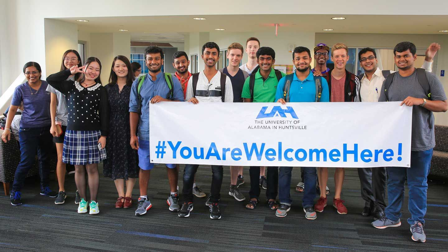 International students holding a UAH welcome sign
