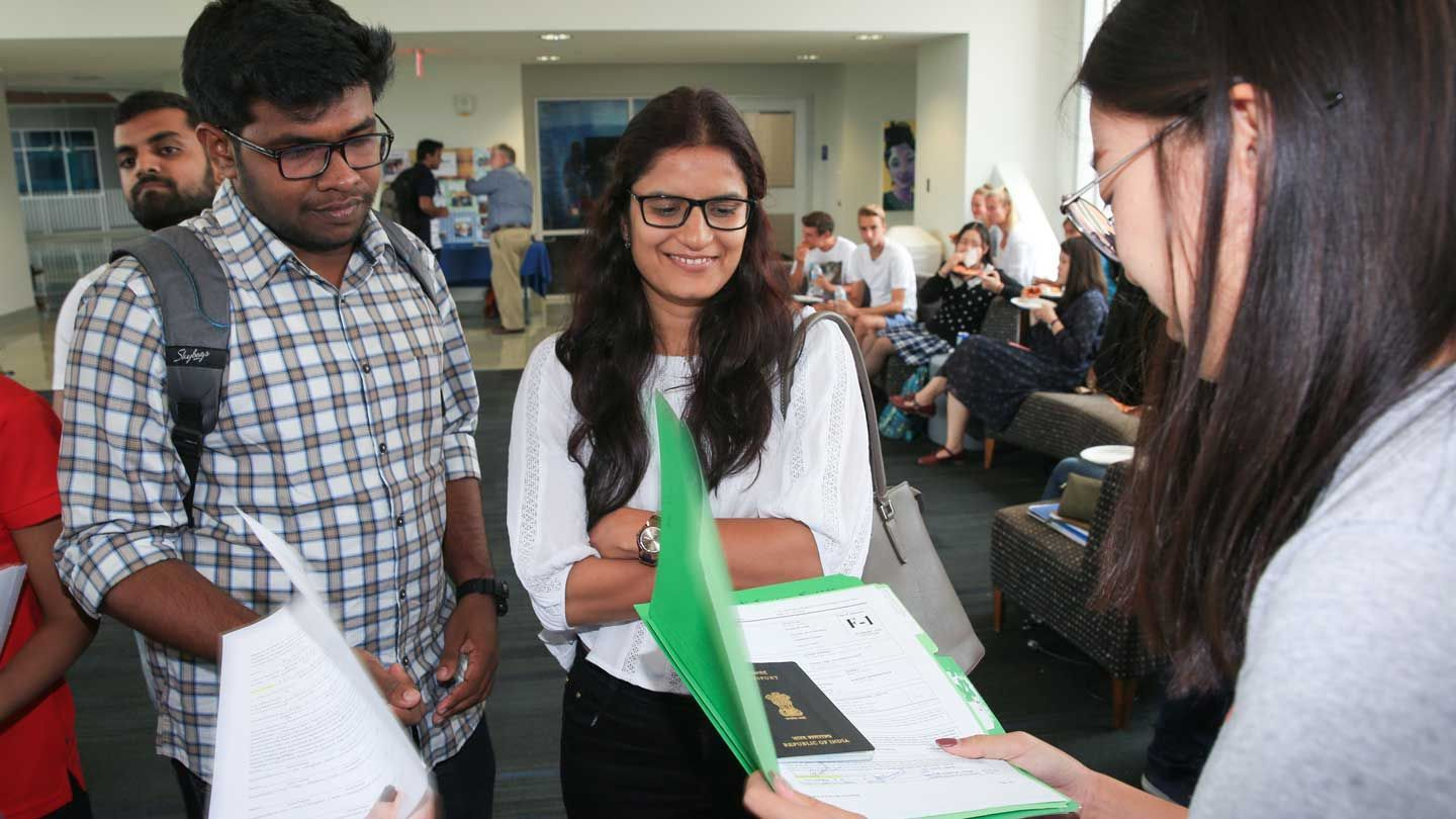 International students looking at the contents in a folder