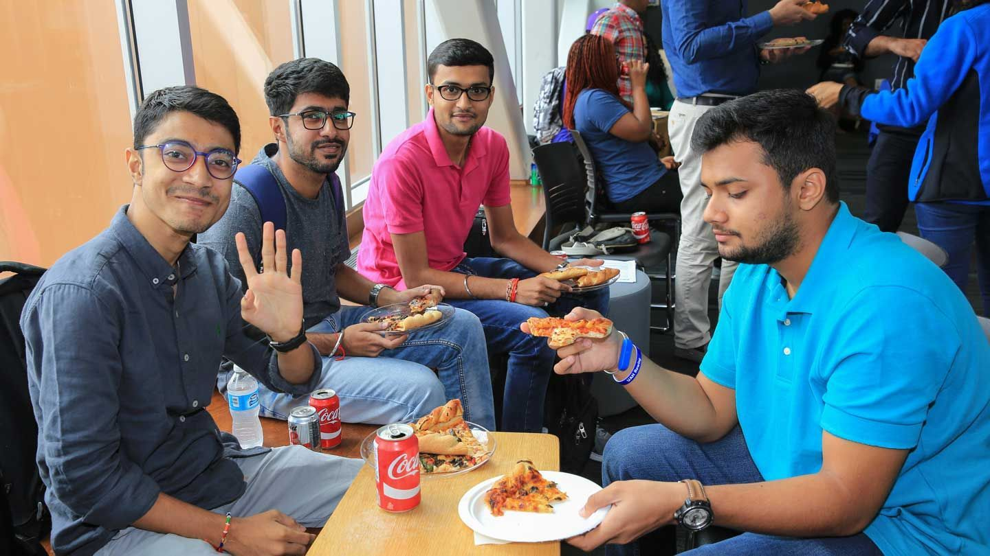 International men students smiling and eating pizza