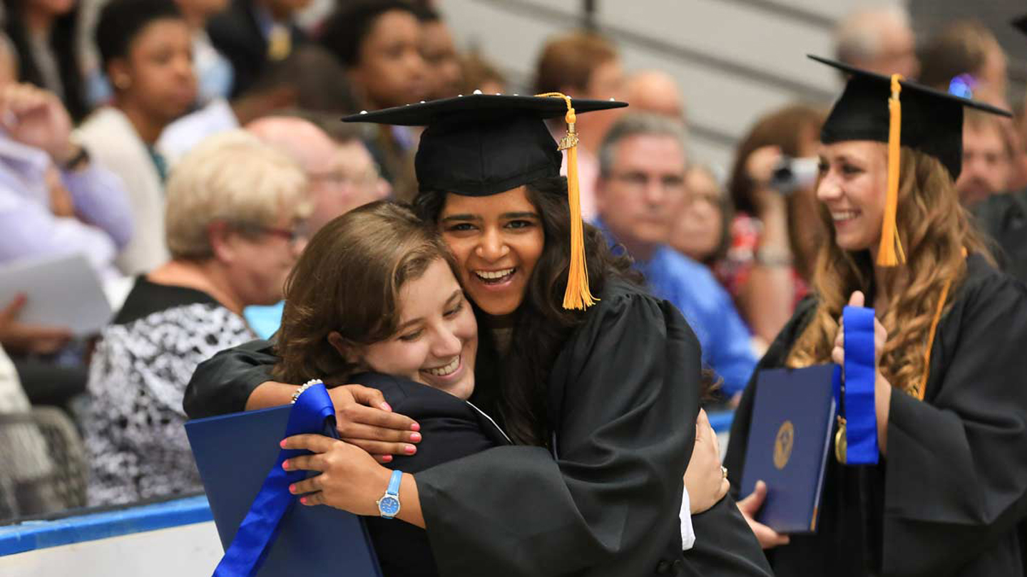 Graduates hugging at commencement