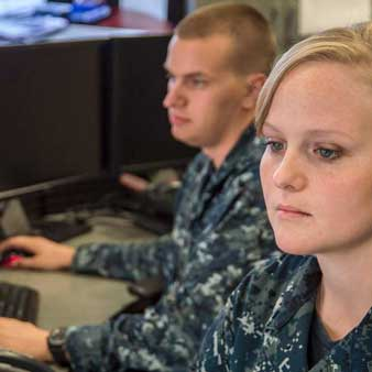 Student dressed in a Navy NWU Type I uniform working at a computer.
