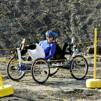 Two students pedal a lunar rover around a racecourse