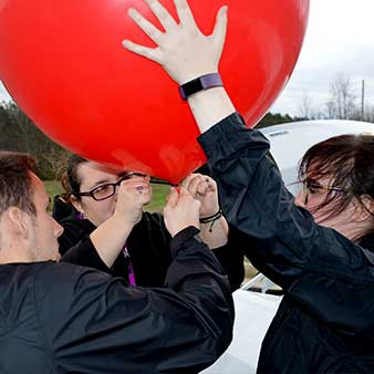 students holding a weather balloon