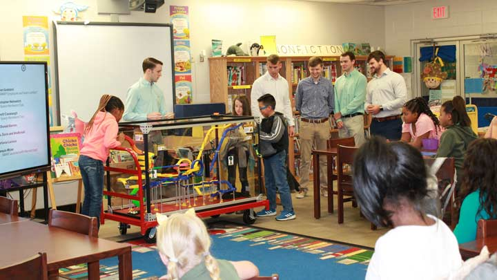 Students and children standing around the Mobile STEM Roller Coaster in an elementary classroom.