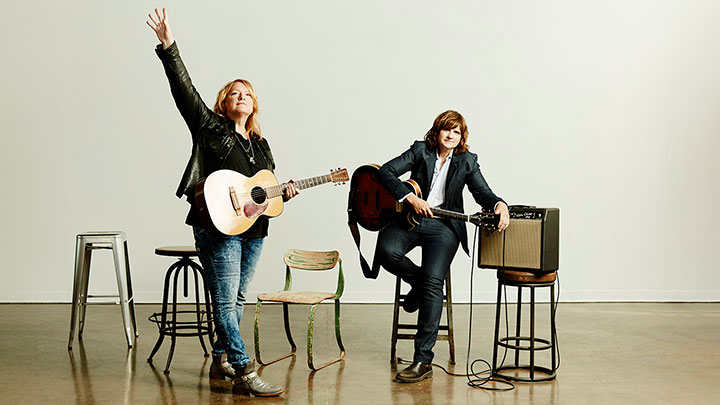 Indigo Girls standing on a stage holding guitars