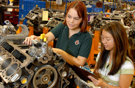 Two students working on an engine