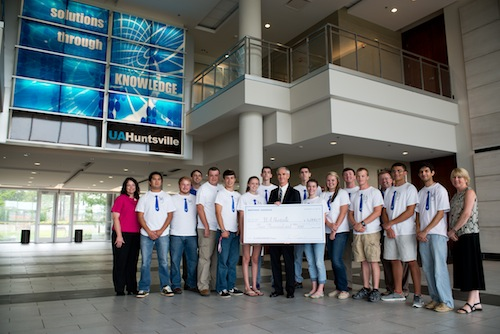 Vice President and Corporate Lead Executive for Northrop Grumman in Huntsville, Retired Lt. General Kevin Campbell provides a $4,000 check to UAHuntsville for the university's engineering education efforts. Posing with Campell are UAHuntsville engineering students and local high school students interested in the engineering field.