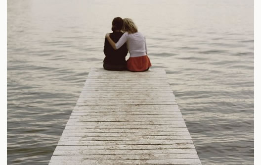 two people sitting at the end of a pier
