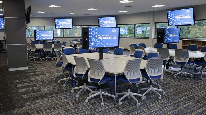 The New College of Business Cybersecurity Lab featuring several large tables and seating and tv screens.