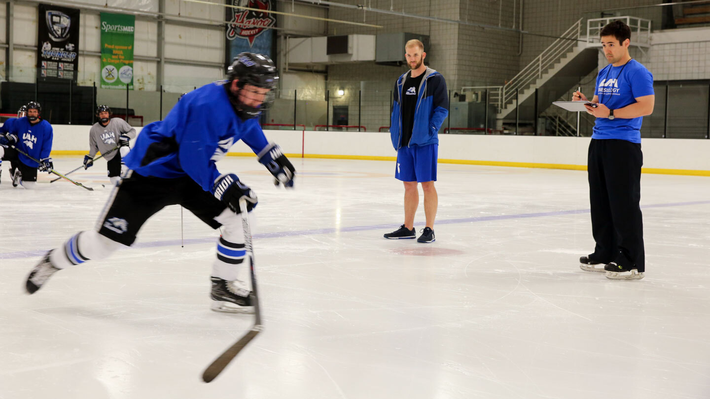 Hockey player on the ice monitored by a coach.