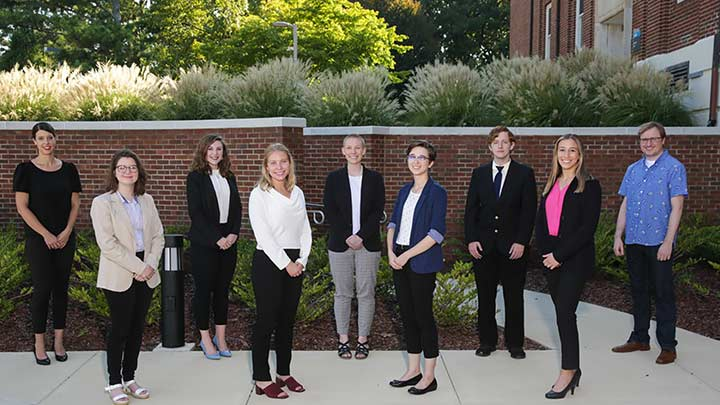 INCLUDE team posing outside at UAH in front of a brick wall.
