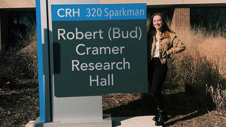 Emily Wisinski standing next to the Robert Cramer Research Hall building sign