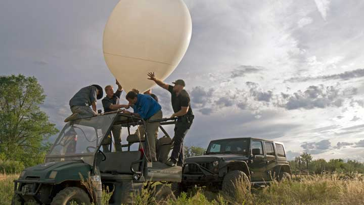 Five people standing on an offroad vehicle maneuvering a surveillance balloon on Skinwalker Ranch