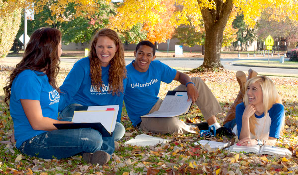 Students enjoying themselves on the campus of UAH under a tree with bright yellow leaves