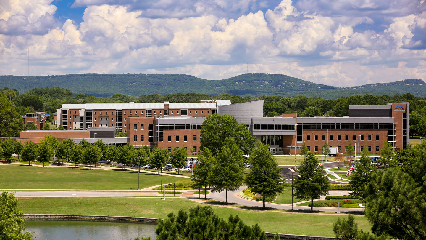 the campus of the university of alabama in huntsville with mountains in the background