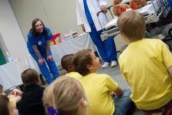 A nurse interacts with kids at the Let's Pretend Hospital.