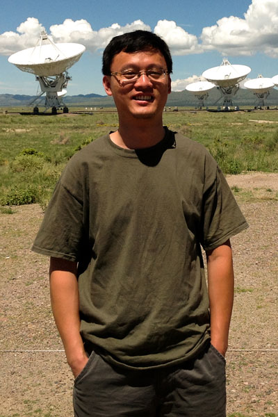 Xiaocan Li near an antenna array in New Mexico.