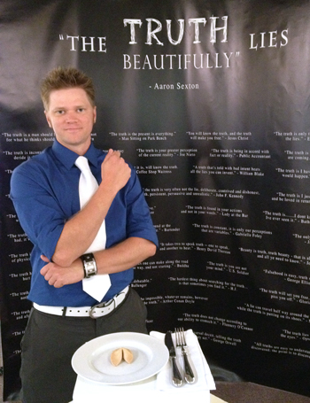 Aaron Sexton stands in front of a backdrop that reads: 'The Truth Lies Beautifully'