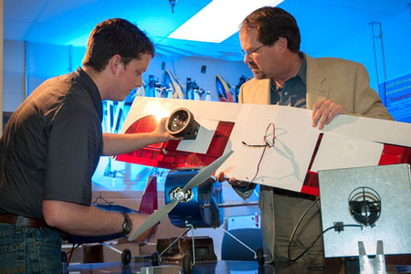Mechanical Engineering student Josiah Thomas (left), and Dr. D. Brian Landrum, associate professor of Aerospace Engineering at UAH, discuss placement of a solar blind fire sensor on a UAV (unmanned aerial vehicle).