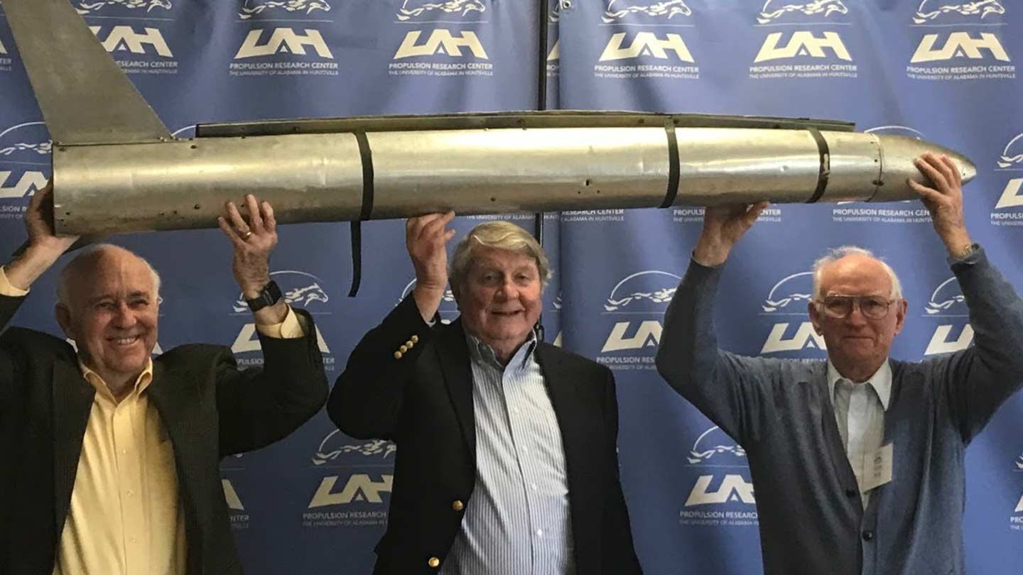 Bill Snoddy, Dr. Robert Naumann, and Harry Reid pose with a replica of Explorer 1