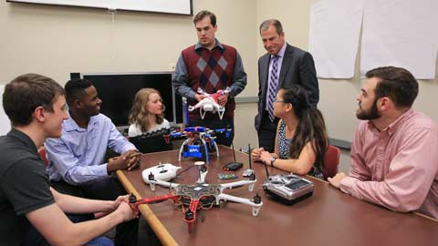 A UAH senior design class explains their strategy for drone defense to Bob McCaleb, Northrop Grumman corporate lead executive, at Olin B. King Technology Hall on campus. From left are Daniel Bernues, Tevon Walker, Alyse Adams, William Klingbeil, McCaleb, Faith Buckley and Zack Horvath.