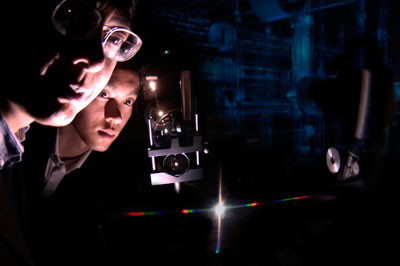 Dr. Junpeng Guo, UAHuntsville Associate Professor of Electrical Engineering and Optics, and doctoral student Haisheng Leong view the spectra from a new nanoscale photonic device called a super nano-grating.