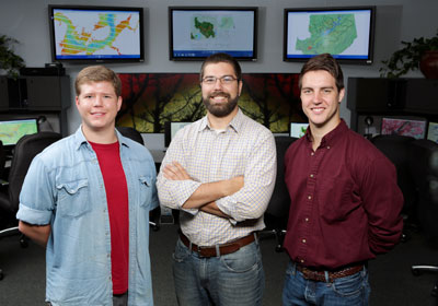 UAH seniors Casey Calamaio and Kel Markert flank their advisor Dr. Rob Griffin in the NASA SERVIR Earth Science Student Research lab at the National Space Science and Technology Center on campus. Behind them on the monitors is a vegetation index of Guntersville Lake, a sub-watershed analysis map around Guntersville and a map showing their study area.