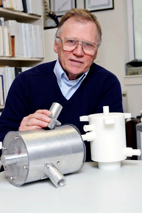 Dr. James Blackmon in his office with plastic models of the rotary valve made with a 3-D printer and a stainless steel version.