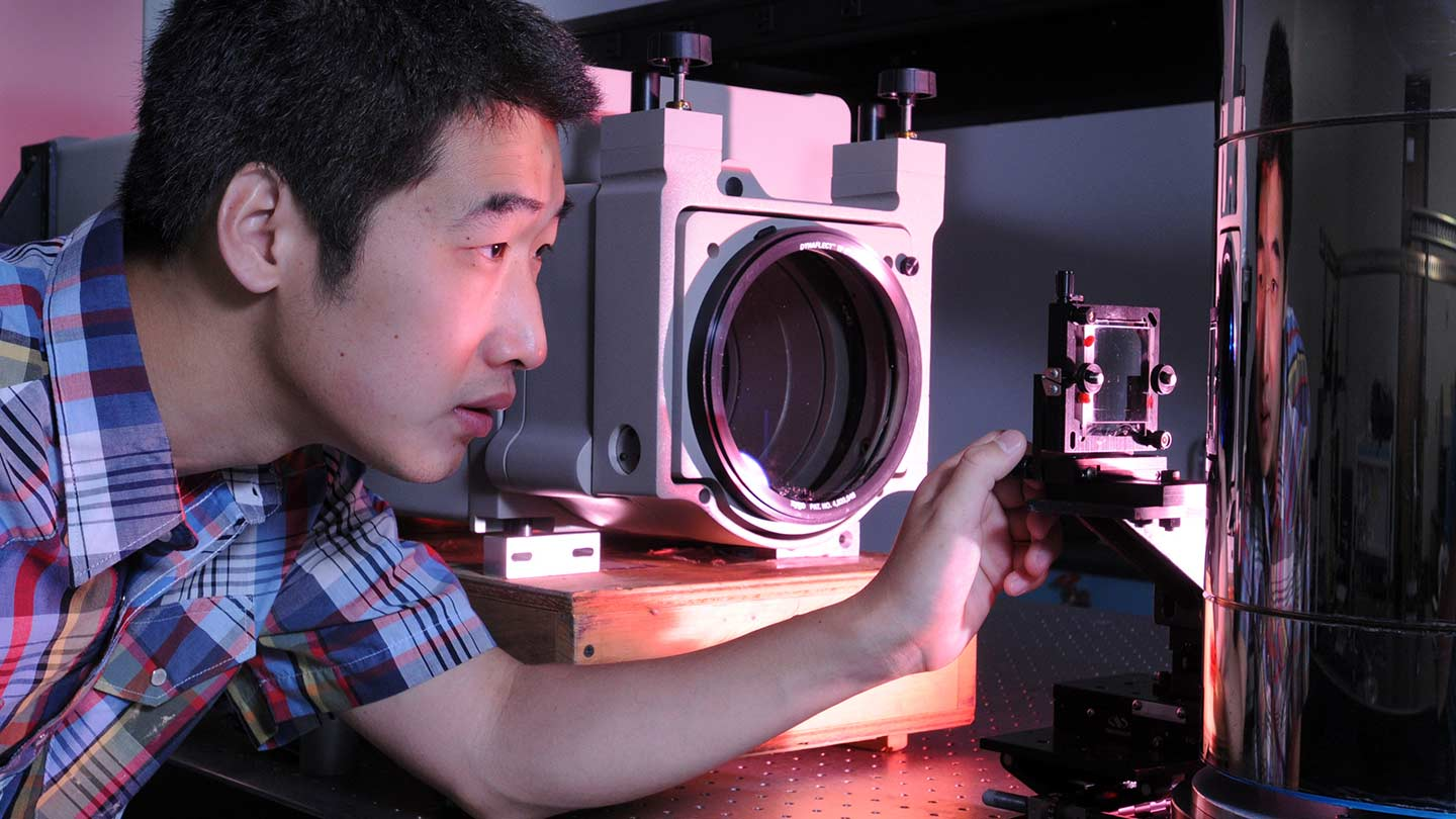 Students and professor work on nanoprobe sensor in Optics lab.