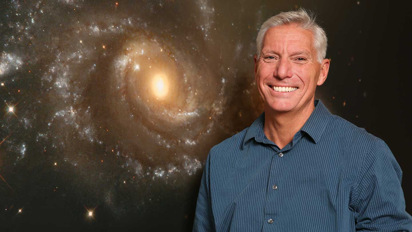 Dr. Gary Zank standing in front of a space background.