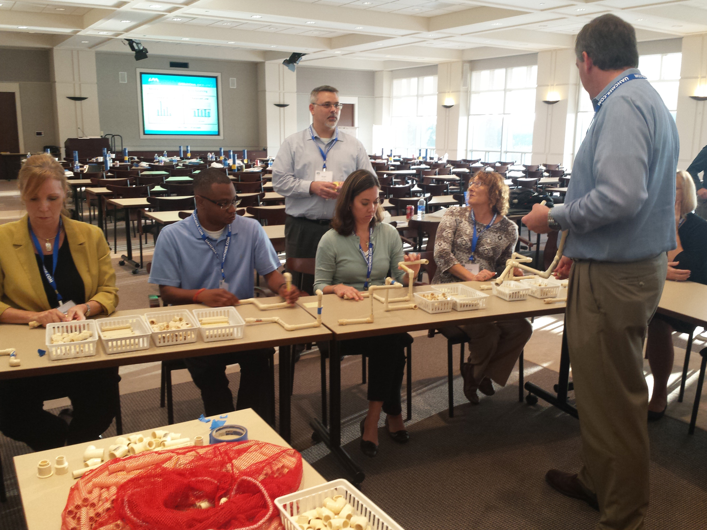 OOE Lean Six Sigma Practitioners Brian Tucker and Joe Paxton assist students during the LSS Yellow Belt Simulation at the Alabama LSS Conference 2015.