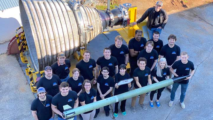 Group photo of student team members holding rocket.